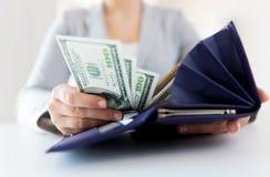 Sluit omhoog van vrouwenhanden met portefeuille en geld stock fotografie