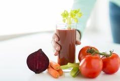 Sluit omhoog van vrouwenhanden met sap en groenten Stock Fotografie