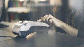 Sluit omhoog van vrouwens hand betalend met een creditcard in een opslag Ga de SPELDcode in Stock Fotografie