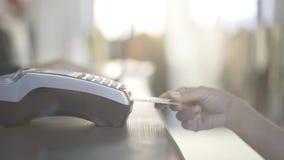 Sluit omhoog van vrouwens hand die met een creditcard in een opslag betalen en haar aankoop nemen royalty-vrije stock afbeeldingen