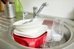 Sluit omhoog van vuile schotels die in keukengootsteen wassen Stock Afbeelding