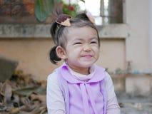 Sluit omhoog van weinig Aziatische zitting van het babymeisje en het glimlachen aangezien zij in een goede stemming is stock afbeeldingen