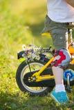 Sluit omhoog van weinig jong geitjejongen die op zijn fiets met bloemen berijden, in openlucht Jongen die zijn eerste gele fiets  royalty-vrije stock foto