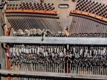Sluit omhoog van werktuigkundigen binnen van een rechte doorstane antiquiteit gebroken rustieke piano in openlucht in de woestijn royalty-vrije stock foto