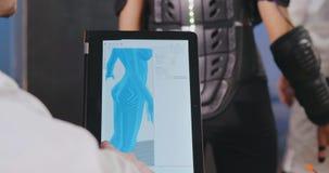 Sluit omhoog van wetenschapper die 3d model van exoskeleton op tablet onderzoeken stock footage