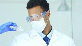 Sluit omhoog van wetenschapper die reactie in horlogeglas bestuderen in laboratorium stock footage
