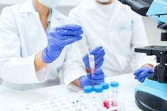 Sluit omhoog van wetenschappers die reageerbuis in laboratorium vullen royalty-vrije stock afbeelding