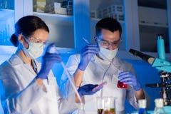 Sluit omhoog van wetenschappers die test in laboratorium maken stock afbeeldingen