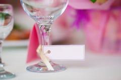 Sluit omhoog van wijnglas en naamkaart Dien het plaatsen in Stock Foto's