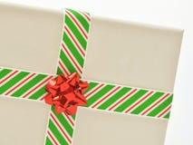 Sluit omhoog van wit die canvas in Kerstmislint wordt verpakt, dat gestreepte rood, wit en groen is, met rode boog, op wit royalty-vrije stock fotografie