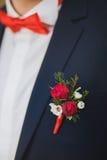 Sluit omhoog van wit en rood toenam corsage op mensenkostuum Royalty-vrije Stock Foto's