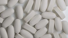 Sluit omhoog van witte capsules roteren op lijst Apotheek antibiotische pillen stock videobeelden