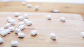 Sluit omhoog van witte suiker op houten raad of lijst stock videobeelden