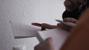 Sluit omhoog van zakenman het schrijven op notitieboekje voorraad De handen van bedrijfsmensen maken nota's in een notitieboekje stock videobeelden