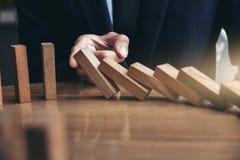 Sluit omhoog van zakenmanhand die Dalende houten Domino's EF tegenhouden stock afbeeldingen