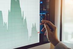 Sluit omhoog van zakenmanhand richtend aan effectenbeursgrafiek en analyse van het computerscherm stock fotografie