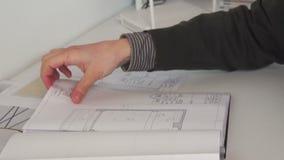 Sluit omhoog van zeker architectenmannetje die met architecturaal plan werken stock footage