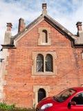Sluit omhoog van zij de baksteenvensters van de kerkzaal boven rode auto stock foto's