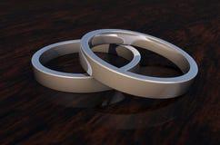 Sluit omhoog van 2 Zilveren Ringen van Shinny op Woodenbase Stock Fotografie
