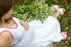 Sluit omhoog van zwangere buik in aard meisje in een witte kleding op een bloemgebied met margrieten Het concept van de liefde royalty-vrije stock afbeelding