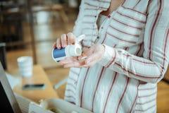 Sluit omhoog van zwangere vrouw die vitamine zetten in haar palm royalty-vrije stock foto's