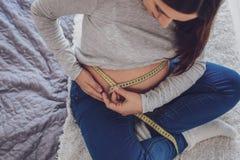 Sluit omhoog van zwangere vrouw met het meten van hulpmiddel stock fotografie