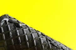 Sluit omhoog van zwart wafeltje tegen gele achtergrond Lege ruimte voor tekst De idylle van de zomer royalty-vrije stock afbeeldingen