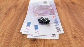 Sluit omhoog van zwarte dobbelen en euro contant geldgeld Stock Fotografie