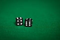 Sluit omhoog van zwarte dobbelen op groene casinolijst Stock Afbeelding