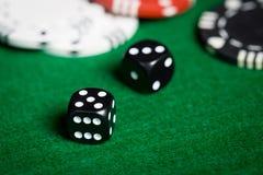 Sluit omhoog van zwarte dobbelt op groene casinolijst Stock Foto