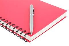 Sluit omhoog verbindende notitieboekjespiraal - en pen op witte achtergrond Royalty-vrije Stock Foto