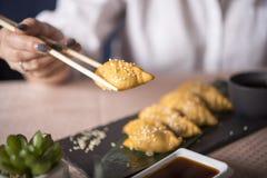Sluit omhoog vers gekookt dumplingss op steenlei Chinese bollen met sesamzaden op een groen blad Vrouw het eten stock foto