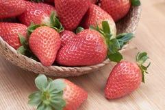 Sluit omhoog verse aardbeien met natuurlijke houten achtergrond in een mand stock foto