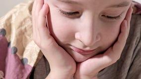 Sluit omhoog video van het gezicht die van een jongen op een bed, het ontspannen en het letten op video op smartphone thuis ligge stock footage
