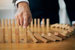 Sluit omhoog vingerzakenman die houten blok van het vallen in de lijn van domino met risicoconcept tegenhouden stock foto