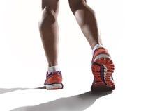 Sluit omhoog voeten met loopschoenen en vrouwelijke sterke atletische benen van de jogging van de sportvrouw royalty-vrije stock afbeeldingen