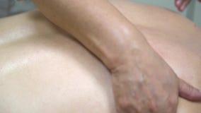 Sluit omhoog voor fysiotherapeuthanden die achtermassage doen aan geduldig liggen, gezondheidszorg, ontspanningsconcept Olieachti stock video