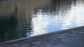 Sluit omhoog voor grijze stoep dichtbij een rivier met een fontein voorraad Geasfalteerd voetpad dichtbij donker water van de riv stock video