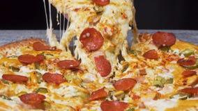 Sluit omhoog voor hand die een plak van pizza met het uitrekken van mozarella op zwarte achtergrond nemen, foodporn concept Kader stock footage