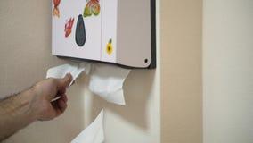 Sluit omhoog voor mensenhanden die weefsels van witte plastic doos met bloem en vlinderstickers in badkamers trekken wit stock afbeelding