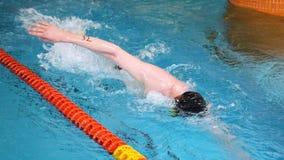 Sluit omhoog voor professionele zwemmer in langzame mothion terwijl het zwemmen van race in binnenpool Atleet opleiding, zwemmen stock footage
