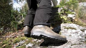 Sluit omhoog voor wandelingsrubberlaarzen in actie betreffende een rotsachtige weg Mannetje die stappen maken om een berg in een  royalty-vrije stock afbeelding
