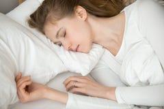 Sluit omhoog vreedzame kalme jonge vrouwenslaap in comfortabel bed stock afbeeldingen