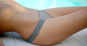 Sluit omhoog Vrouw in Bikini Liggend door Zwembad stock videobeelden