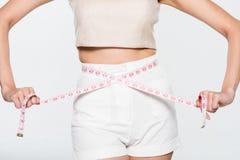 Sluit omhoog Vrouw die haar taille met maatregelenlijn meten Stock Foto's