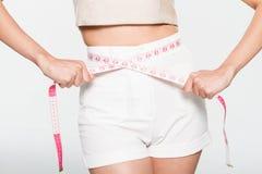 Sluit omhoog Vrouw die haar taille met maatregelenlijn meten Royalty-vrije Stock Foto's