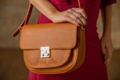 Sluit omhoog vrouw met oranje in hand zak De herfstuitrusting stock foto