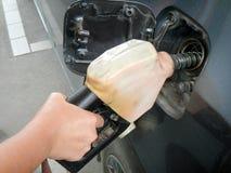 Sluit omhoog vrouwelijke de hand pompende brandstof van ` s door automaat in auto's bij benzinestation Het concept van het vervoe royalty-vrije stock fotografie