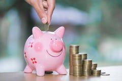 Sluit omhoog vrouwelijke hand zettend muntstuk in spaarvarken, sparen geld voor toekomst royalty-vrije stock foto