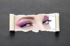 Sluit omhoog vrouwelijke ogen met heldere samenstelling op grijs gescheurd document stock afbeeldingen